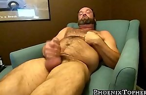 Hairy mature bear plays with his rock..